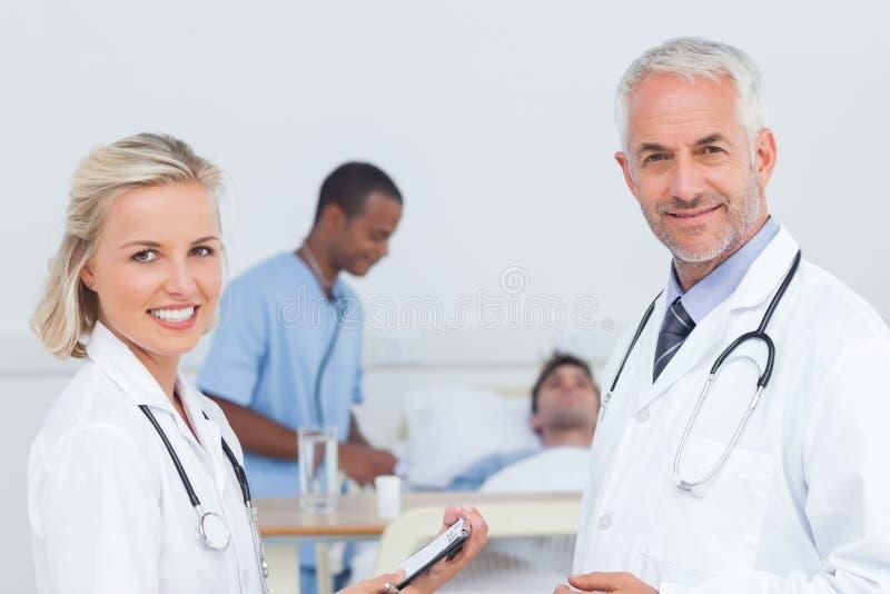 Χαμογελώντας γιατροί που στέκονται μπροστά από τον ασθενή στοκ φωτογραφίες με δικαίωμα ελεύθερης χρήσης