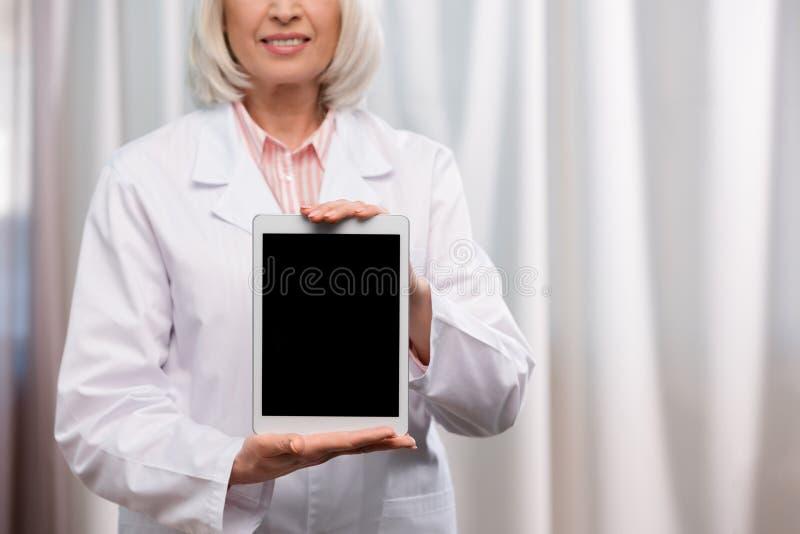 Χαμογελώντας γιατρός στο άσπρο παλτό που παρουσιάζει ταμπλέτα στα χέρια στοκ φωτογραφίες με δικαίωμα ελεύθερης χρήσης