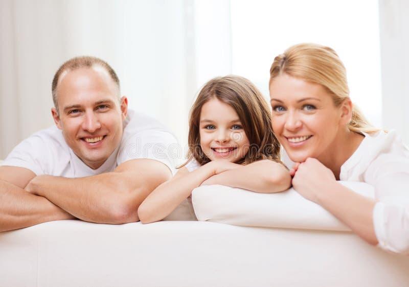 Χαμογελώντας γονείς και μικρό κορίτσι στο σπίτι στοκ φωτογραφία
