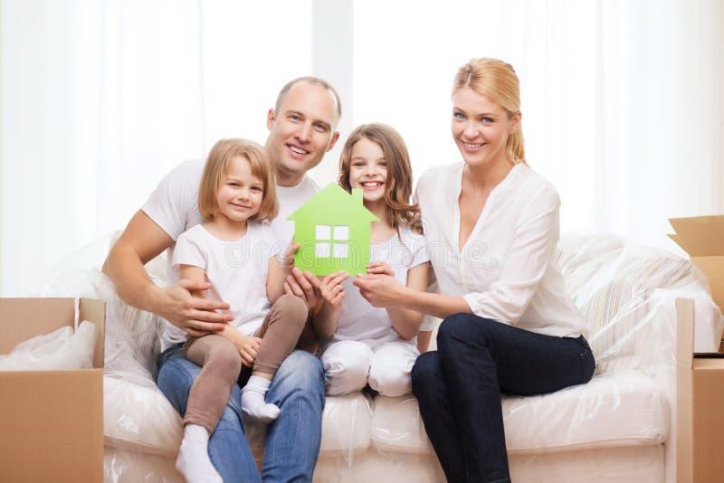 Χαμογελώντας γονείς και δύο μικρά κορίτσια στο νέο σπίτι στοκ εικόνες