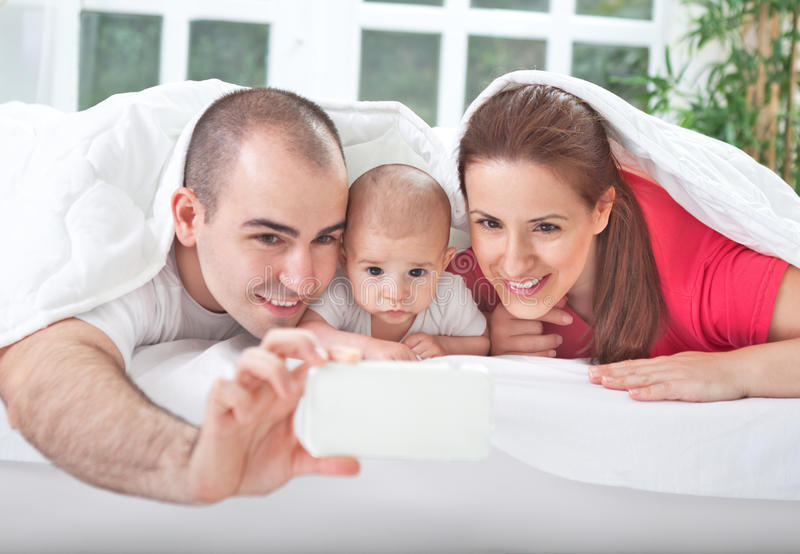 Χαμογελώντας γονείς με το μωρό που παίρνει την οικογενειακή φωτογραφία στοκ φωτογραφία