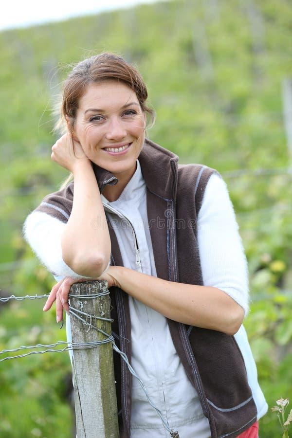Χαμογελώντας γυναίκα αγροτών στους αμπελώνες στοκ εικόνα