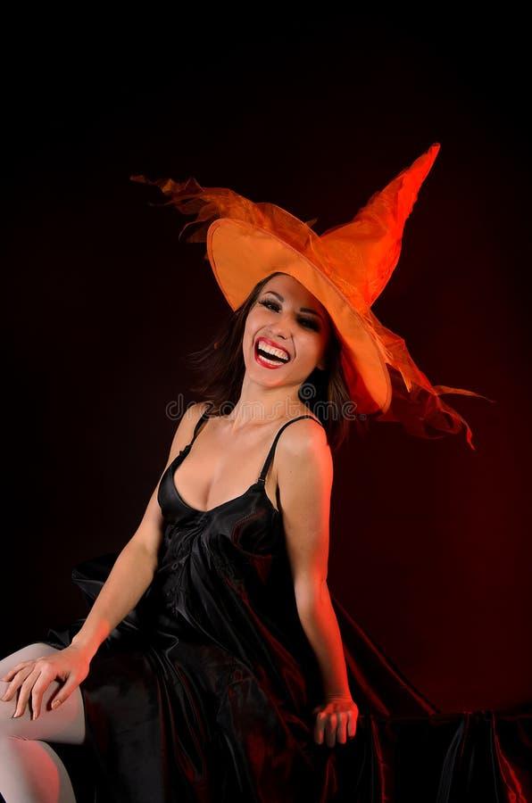 Χαμογελώντας γυναίκα δειγμένο στο πορτοκάλι καπέλο στοκ φωτογραφία