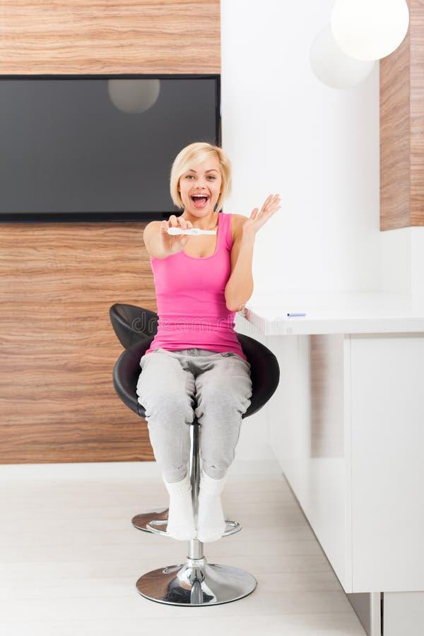 Χαμογελώντας γυναίκα θετικού αποτελέσματος δοκιμής εγκυμοσύνης στοκ εικόνες