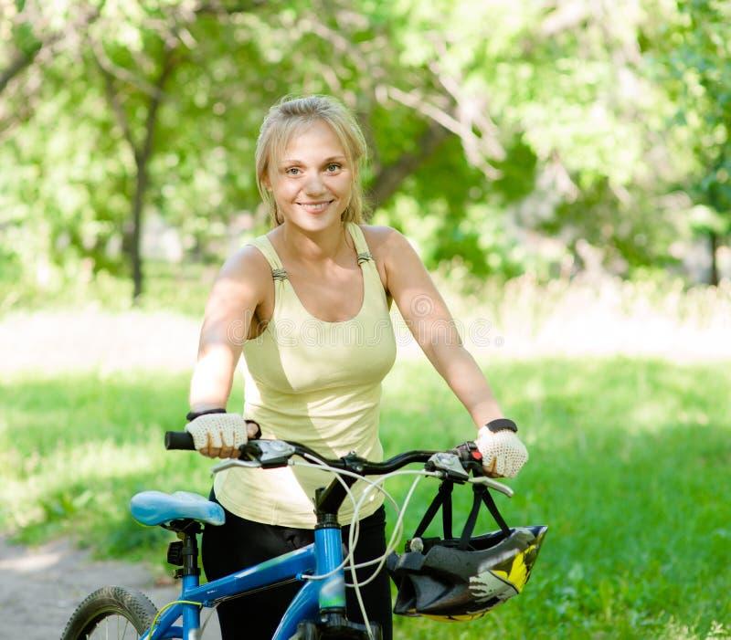 Χαμογελώντας γυναίκα με ένα ποδήλατο βουνών στο πάρκο στοκ φωτογραφία