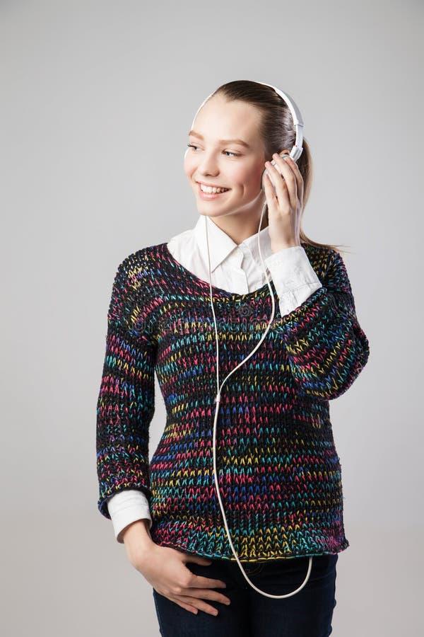 Χαμογελώντας γυναίκα με τα ακουστικά που ακούει τη μουσική στοκ φωτογραφίες με δικαίωμα ελεύθερης χρήσης