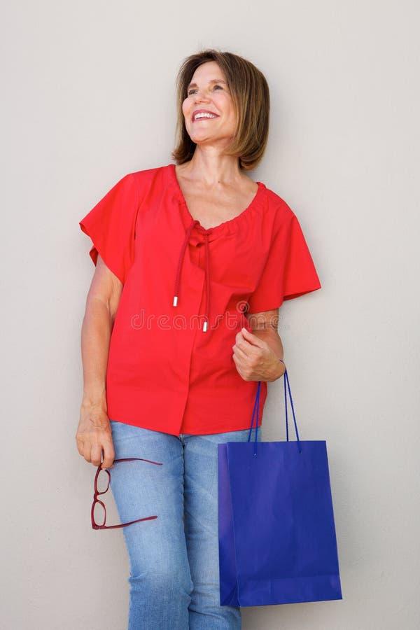 Χαμογελώντας γυναίκα με την τσάντα αγορών και γυαλιά που στέκονται ενάντια στον τοίχο στοκ φωτογραφία με δικαίωμα ελεύθερης χρήσης