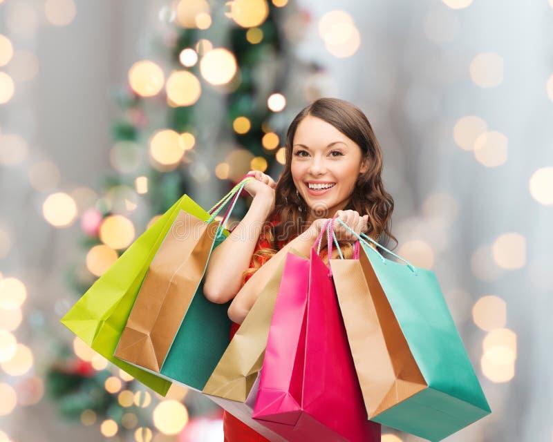 Χαμογελώντας γυναίκα με τις ζωηρόχρωμες τσάντες αγορών στοκ φωτογραφία