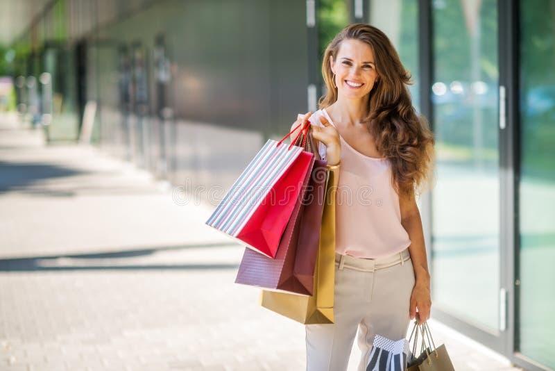 Χαμογελώντας γυναίκα με τις τσάντες αγορών που θέτουν με τις ζωηρόχρωμες τσάντες στοκ φωτογραφία με δικαίωμα ελεύθερης χρήσης