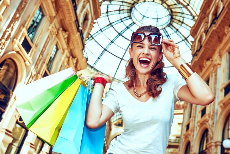 Χαμογελώντας γυναίκα με τις τσάντες αγορών σε Galleria Vittorio Emanuele στοκ εικόνα