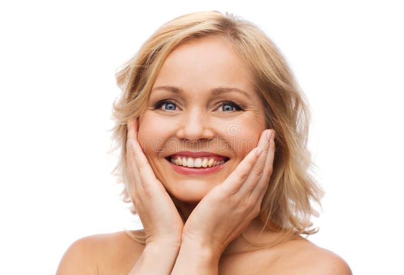 Χαμογελώντας γυναίκα με τους γυμνούς ώμους σχετικά με το πρόσωπο στοκ φωτογραφία