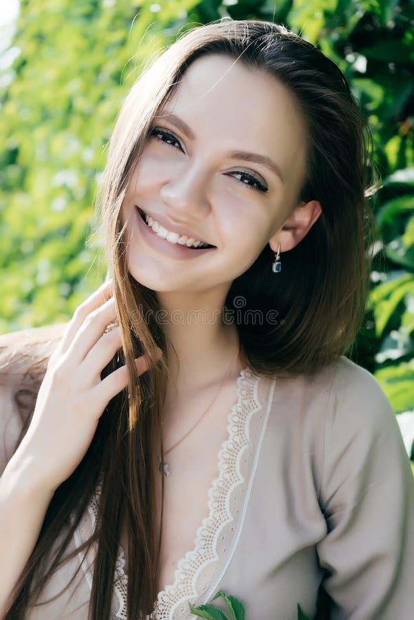 Χαμογελώντας γυναίκα πέρα από το πράσινο θερινό υπόβαθρο φύσης φύλλων στοκ εικόνες