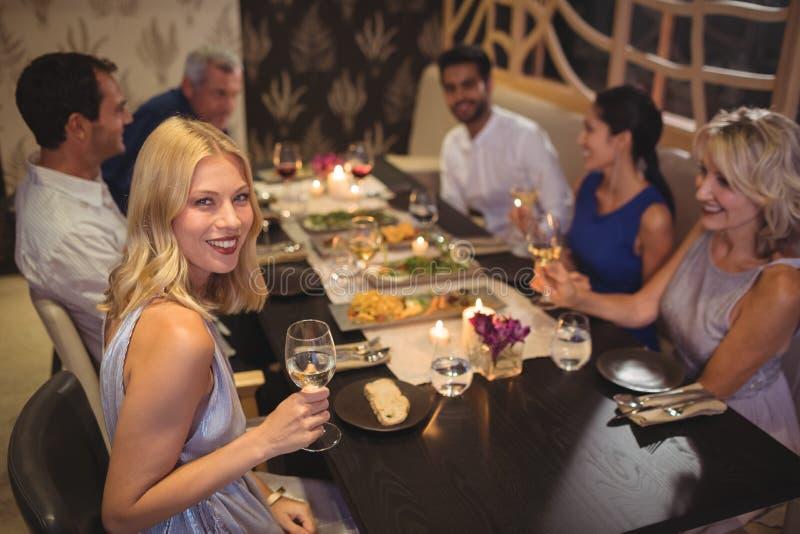Χαμογελώντας γυναίκα που έχει τη σαμπάνια με τους φίλους τους στοκ εικόνα