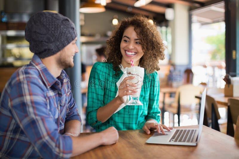 Χαμογελώντας γυναίκα που έχει το καταφερτζή εξετάζοντας την αρσενική συνεδρίαση φίλων από κοινού στοκ φωτογραφία με δικαίωμα ελεύθερης χρήσης