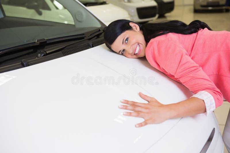 Χαμογελώντας γυναίκα που αγκαλιάζει ένα άσπρο αυτοκίνητο στοκ φωτογραφίες
