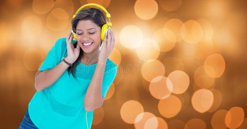 Χαμογελώντας γυναίκα που ακούει τη μουσική στα ακουστικά ενάντια στο bokeh στοκ εικόνες