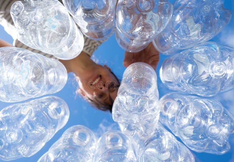 Χαμογελώντας γυναίκα που ανακυκλώνει τα πλαστικά μπουκάλια νερό στοκ εικόνα με δικαίωμα ελεύθερης χρήσης