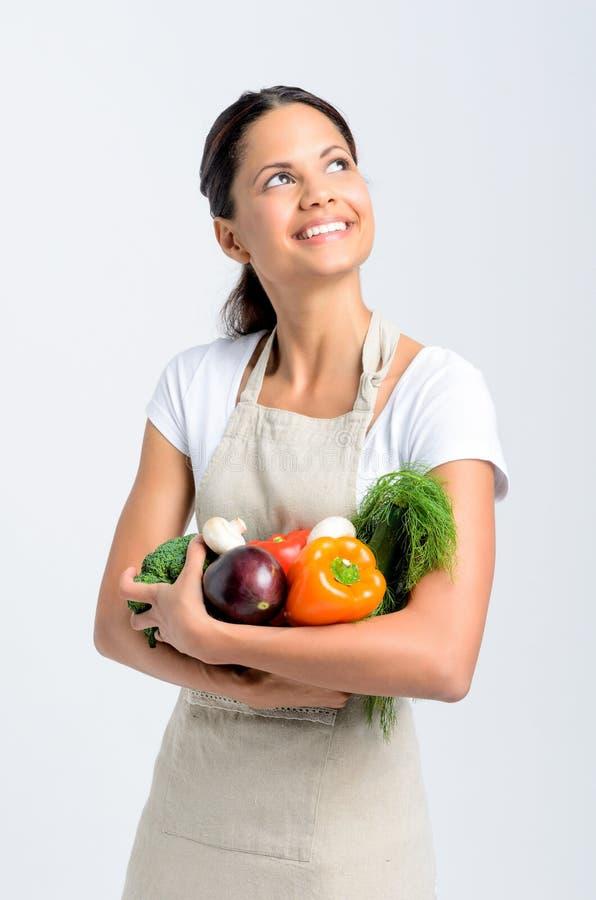 Χαμογελώντας γυναίκα που ανατρέχει με τα φρέσκα προϊόντα στοκ εικόνα