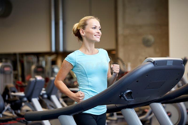Χαμογελώντας γυναίκα που ασκεί treadmill στη γυμναστική στοκ εικόνες με δικαίωμα ελεύθερης χρήσης