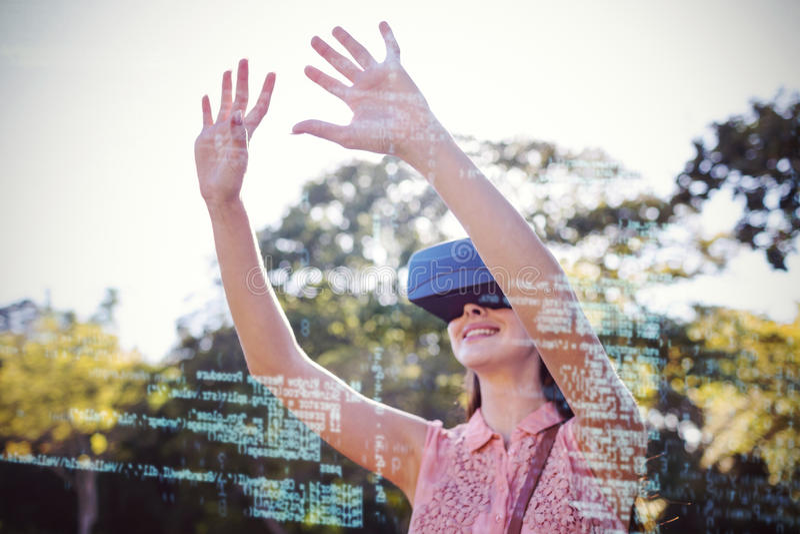 Χαμογελώντας γυναίκα που αυξάνει τα χέρια της χρησιμοποιώντας μια τρισδιάστατη κάσκα VR στο πάρκο στοκ εικόνα με δικαίωμα ελεύθερης χρήσης