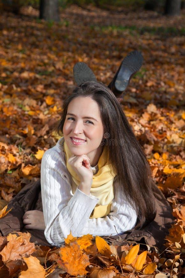 Χαμογελώντας γυναίκα που βρίσκεται στα φύλλα και την απόλαυση του φθινοπώρου στοκ εικόνα
