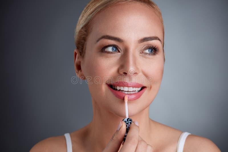 Χαμογελώντας γυναίκα που εφαρμόζει την χείλι-ερμηνεία στα χείλια στοκ φωτογραφία
