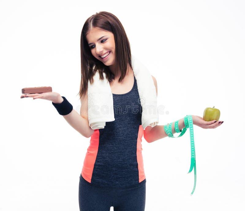 Χαμογελώντας γυναίκα που κάνει την επιλογή μεταξύ των μπανανών και της σοκολάτας στοκ φωτογραφίες
