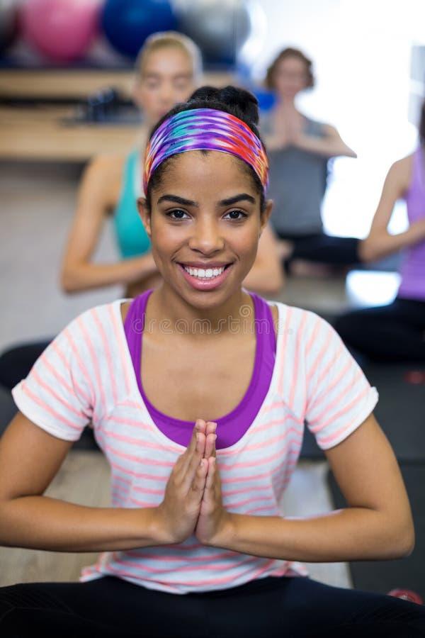 Χαμογελώντας γυναίκα που κάνει τη γιόγκα στη γυμναστική στοκ εικόνα με δικαίωμα ελεύθερης χρήσης