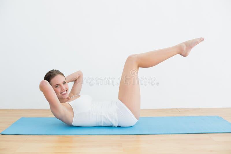 Χαμογελώντας γυναίκα που κάνει τις κρίσιμες στιγμές στομαχιών στο χαλί άσκησης στοκ φωτογραφία με δικαίωμα ελεύθερης χρήσης