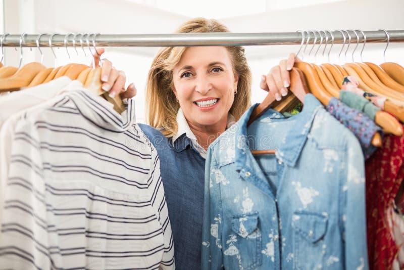 Χαμογελώντας γυναίκα που κοιτάζει μέσω της ράγας ενδυμάτων στοκ φωτογραφία με δικαίωμα ελεύθερης χρήσης
