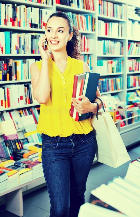 Χαμογελώντας γυναίκα που κουβεντιάζει στο κινητό τηλέφωνο και τη λήψη των βιβλίων στοκ φωτογραφία με δικαίωμα ελεύθερης χρήσης