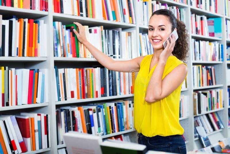 Χαμογελώντας γυναίκα που κουβεντιάζει στο κινητό τηλέφωνο και τη λήψη των βιβλίων στοκ φωτογραφίες