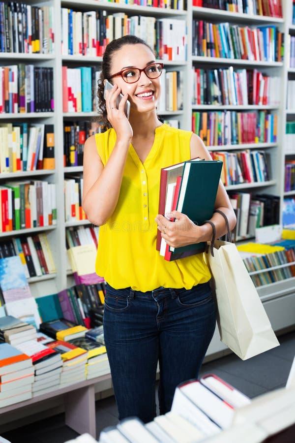 Χαμογελώντας γυναίκα που κουβεντιάζει στο κινητό τηλέφωνο και τη λήψη των βιβλίων στοκ εικόνες με δικαίωμα ελεύθερης χρήσης