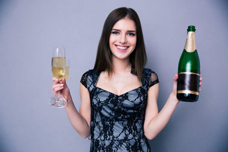 Χαμογελώντας γυναίκα που κρατά το γυαλί δύο και το μπουκάλι της σαμπάνιας στοκ φωτογραφία με δικαίωμα ελεύθερης χρήσης
