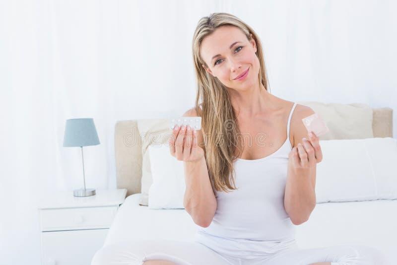 Χαμογελώντας γυναίκα που κρατά το χάπι και το προφυλακτικό στοκ φωτογραφία με δικαίωμα ελεύθερης χρήσης