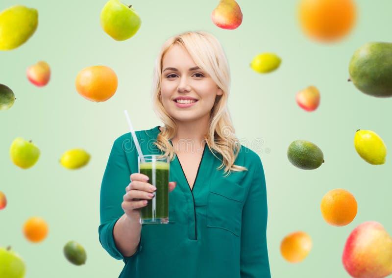 Χαμογελώντας γυναίκα που πίνει το φυτικό χυμό ή το καταφερτζή στοκ φωτογραφίες