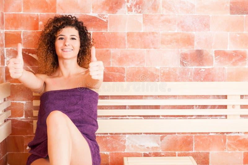 Χαμογελώντας γυναίκα που παρουσιάζει αντίχειρά της καθμένος στη σάουνα στοκ φωτογραφίες