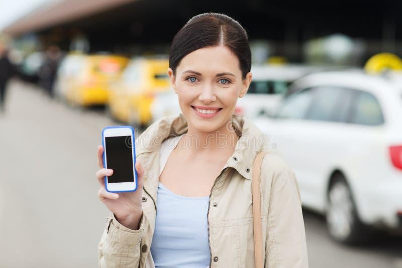 Χαμογελώντας γυναίκα που παρουσιάζει smartphone πέρα από το ταξί στην πόλη στοκ εικόνα με δικαίωμα ελεύθερης χρήσης