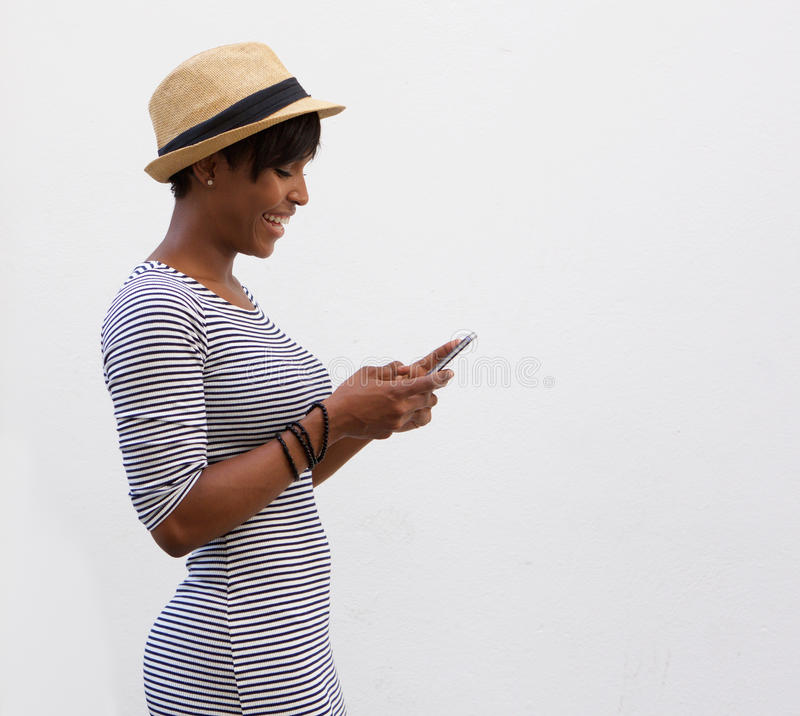 Χαμογελώντας γυναίκα που περπατά και που διαβάζει το μήνυμα κειμένου στοκ εικόνα