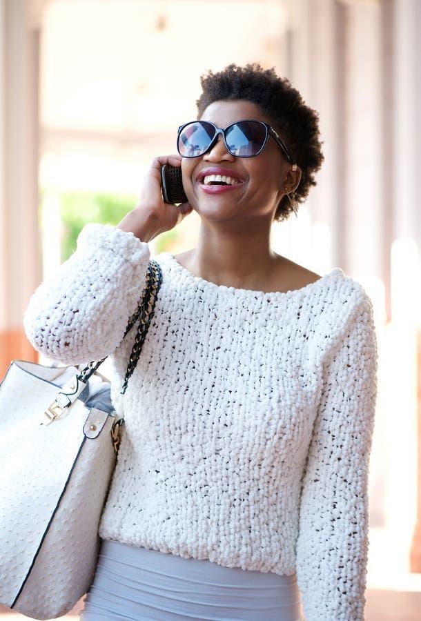 Χαμογελώντας γυναίκα που περπατά και που μιλά στο κινητό τηλέφωνο στοκ εικόνα με δικαίωμα ελεύθερης χρήσης