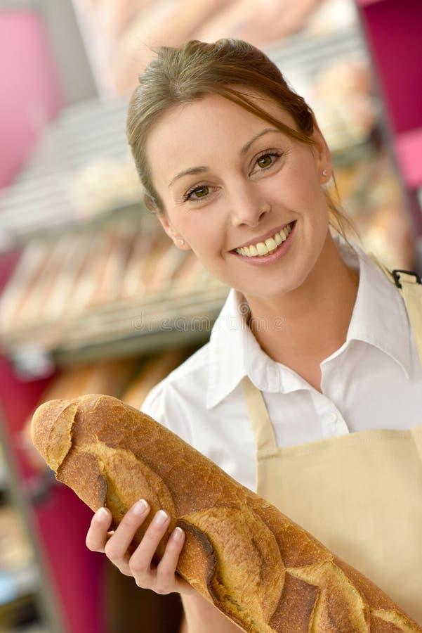 Χαμογελώντας γυναίκα που πωλεί το φρέσκο ψωμί στο κατάστημα αρτοποιείων στοκ εικόνα