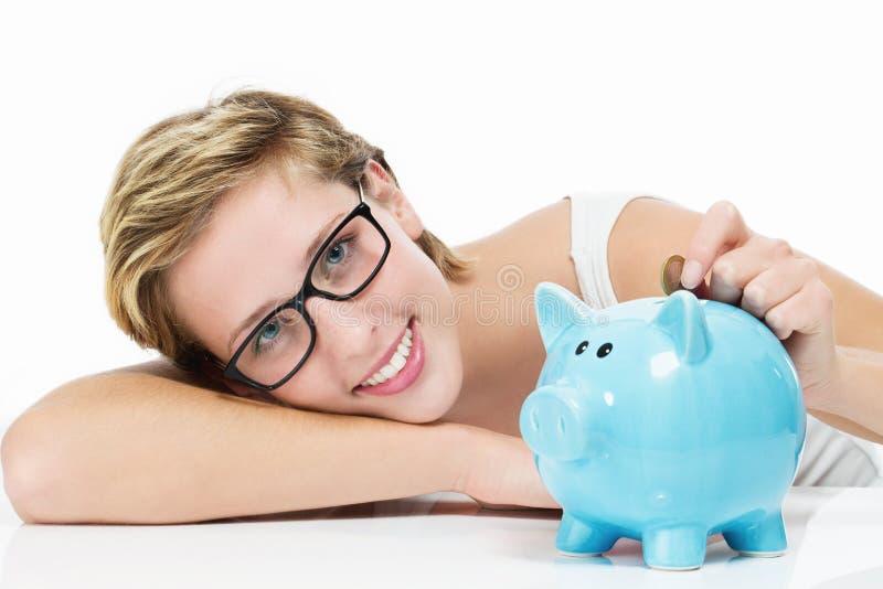 Χαμογελώντας γυναίκα που ρίχνει τα χρήματα στο piggybank της στοκ φωτογραφία