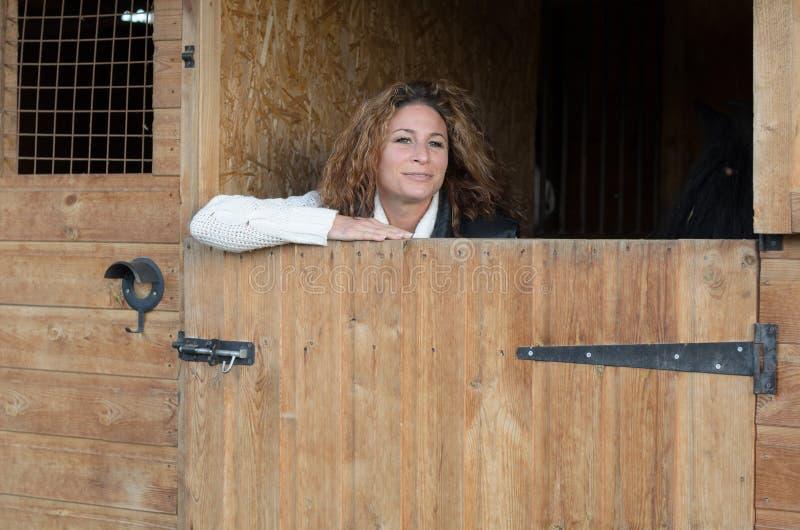 Χαμογελώντας γυναίκα που στέκεται στο σταύλο στοκ φωτογραφία με δικαίωμα ελεύθερης χρήσης