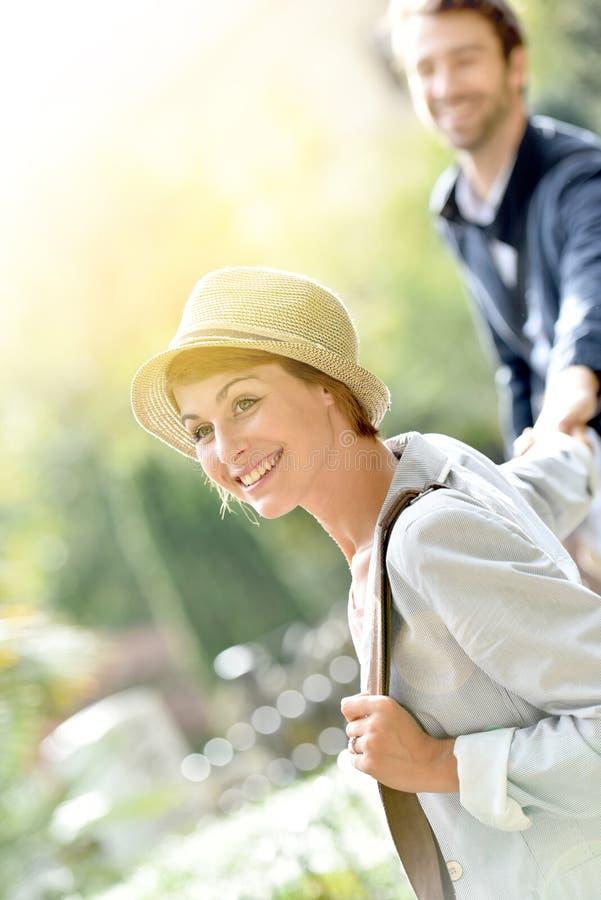Χαμογελώντας γυναίκα που τραβά το χέρι του φίλου υπαίθρια στοκ φωτογραφίες