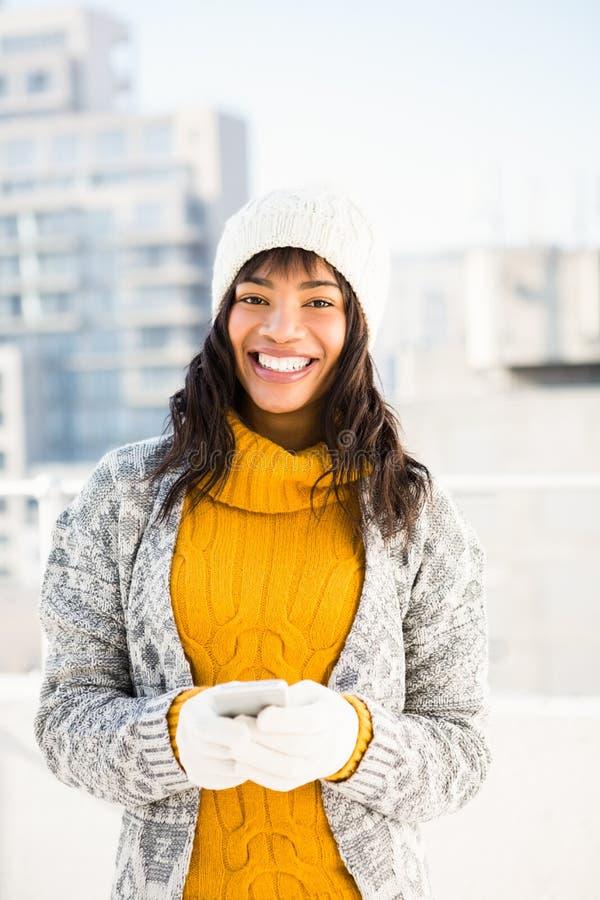 Χαμογελώντας γυναίκα που φορά τα χειμερινά ενδύματα και που δακτυλογραφεί στο τηλέφωνό της στοκ εικόνες με δικαίωμα ελεύθερης χρήσης