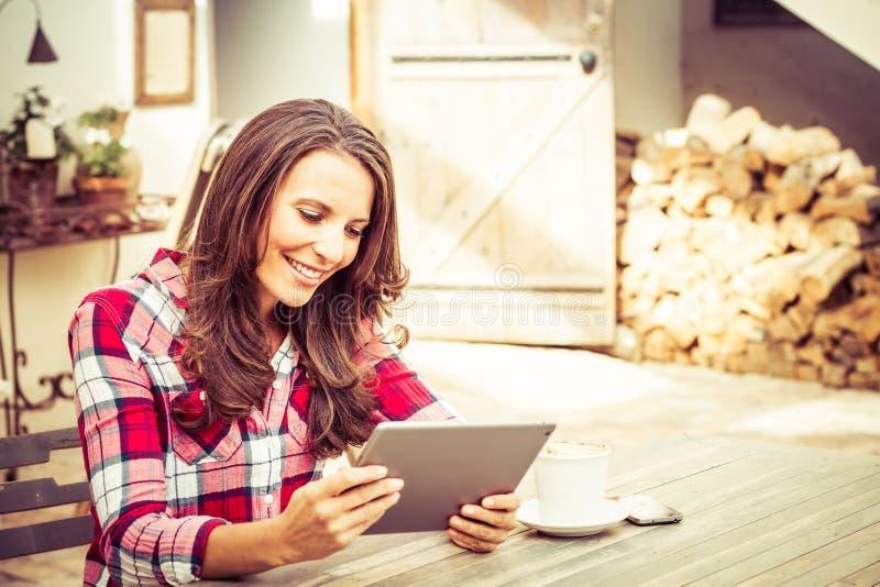 Χαμογελώντας γυναίκα που χρησιμοποιεί την ταμπλέτα στοκ φωτογραφίες