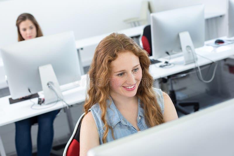 Χαμογελώντας γυναίκα σπουδαστής στην κατηγορία υπολογιστών στοκ εικόνα με δικαίωμα ελεύθερης χρήσης