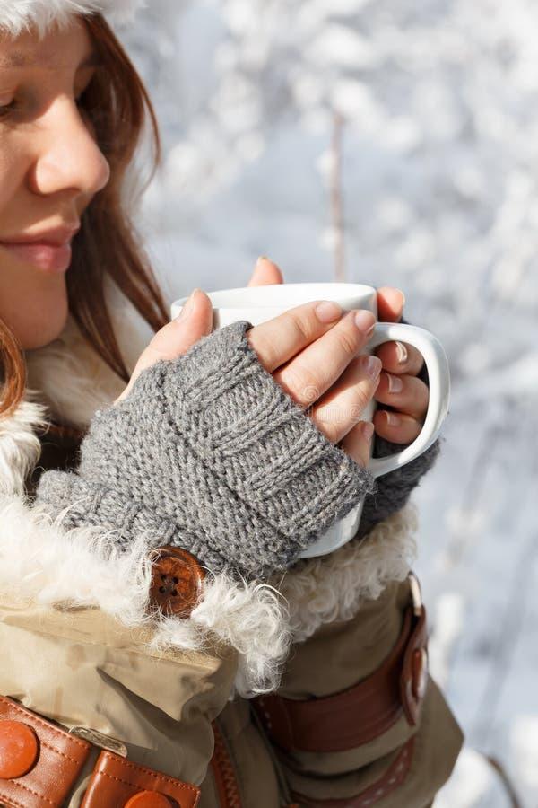 Χαμογελώντας γυναίκα στα γκρίζα γάντια, το παλτό και το καπέλο με το άσπρο holdi γουνών στοκ εικόνα