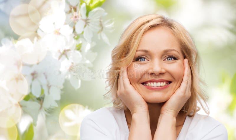 Χαμογελώντας γυναίκα στην άσπρη μπλούζα σχετικά με το πρόσωπό της στοκ εικόνες με δικαίωμα ελεύθερης χρήσης