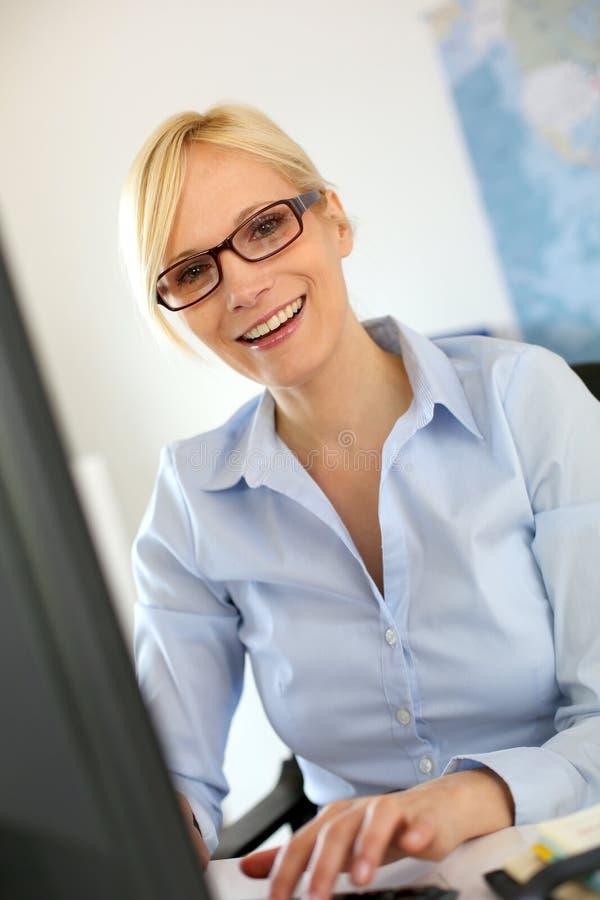 Χαμογελώντας γυναίκα στην εργασία μπροστά από τον υπολογιστή γραφείου στοκ φωτογραφία με δικαίωμα ελεύθερης χρήσης